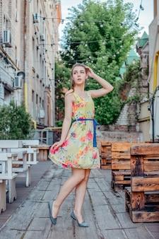 Meisje in jurk loopt in de zomer door de oude stad