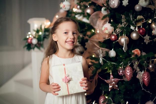 Meisje in jurk met geschenken in de buurt van de kerstboom