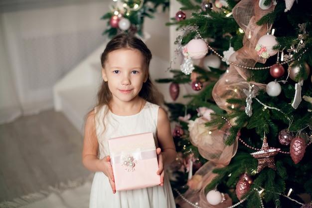 Meisje in jurk met geschenken in de buurt van kerstboom. nieuwjaar.