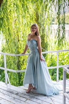 Meisje in jurk op de zomerweg tussen bomen