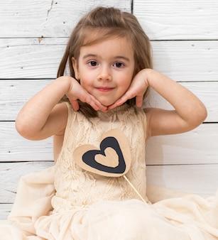 Meisje in jurk zittend op witte houten achtergrond met een hart in handen