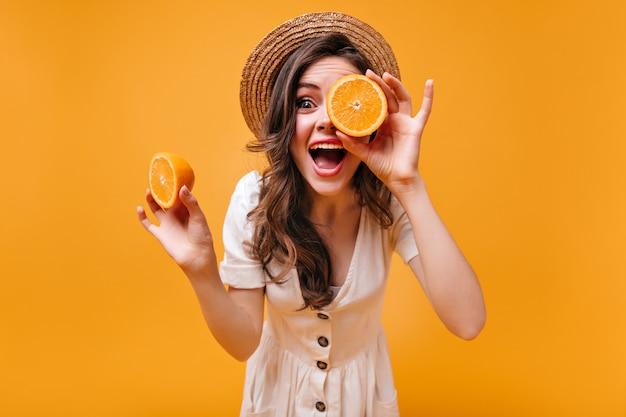 Meisje in katoenen jurk en strooien hoed heeft plezier en poseren met sinaasappels op geïsoleerde achtergrond.