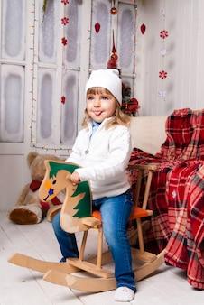 Meisje in kerstdag met paard speelgoed