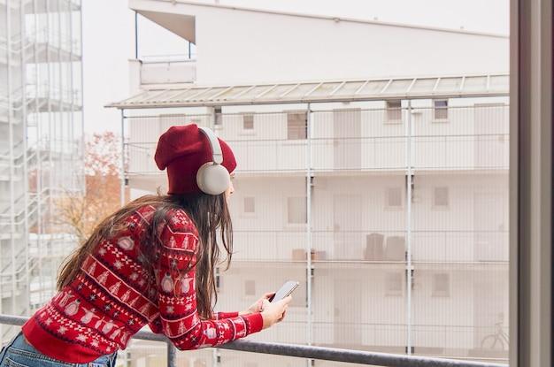 Meisje in kerstkleren luisteren naar muziek. vrouw praten aan de telefoon