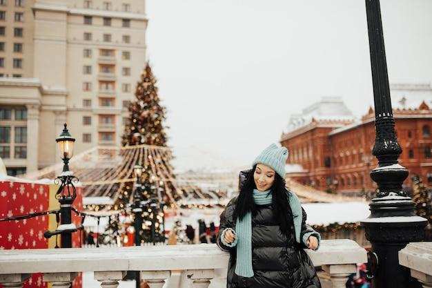 Meisje in kerstmarkt versierd met kerstboom en vakantielichten