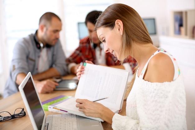 Meisje in klasse die met laptop en schoolboek bestuderen