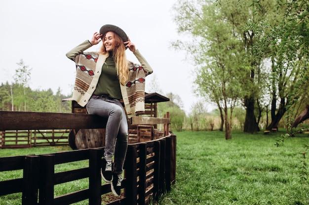 Meisje in kleding met etnische patronen poseren in de achtergrond van het hek op de oude boerderij, het landelijke leven.