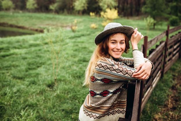 Meisje in kleding met etnische patronen poseren in de natuur muur. portret van lachende jonge vrouw in boho hoed. close-up portret van een meisje in een hoed op de muur van het bos in regenachtige dag.