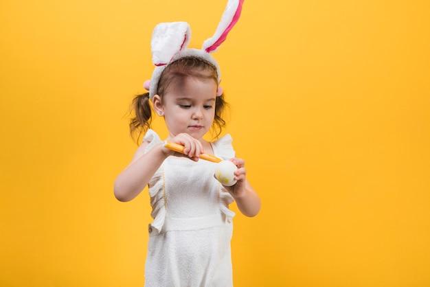 Meisje in konijntjesoren die ei met gevoelde pen schilderen