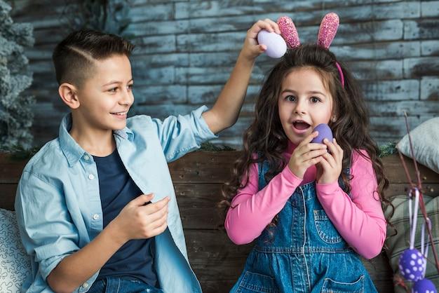 Meisje in konijntjesoren en jongen het spelen met paaseieren