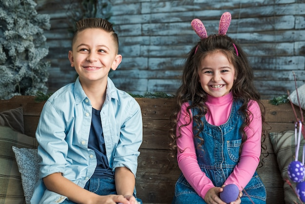 Meisje in konijntjesoren en jongen met paaseieren