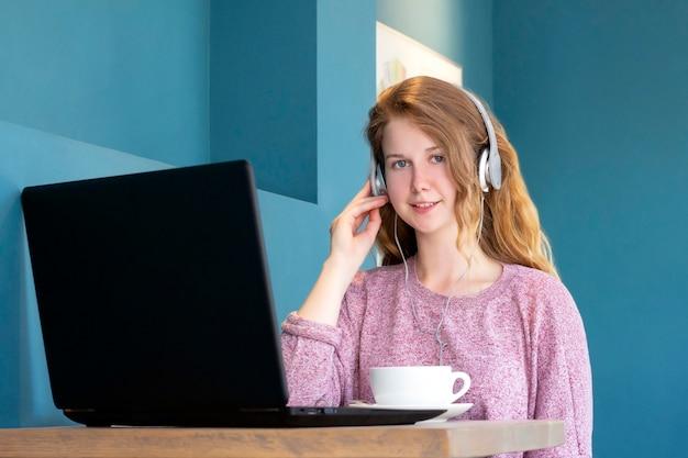 Meisje in koptelefoon communiceert via videochat op een laptop.