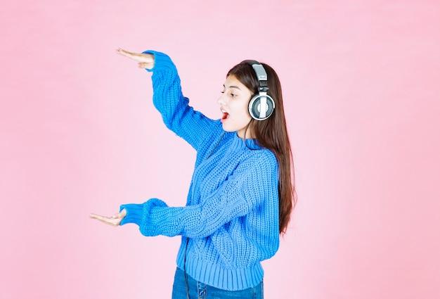 Meisje in koptelefoon met groot formaat teken op roze.