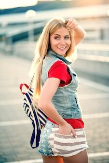 Meisje in korte broek en pigtails loopt in de zomer door de stad met rugzak