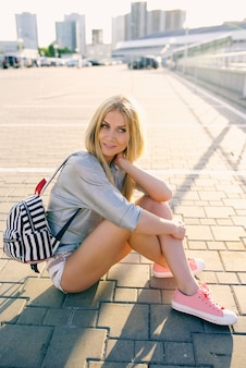 Meisje in korte broek en pigtails zit op de grond met een rugzak
