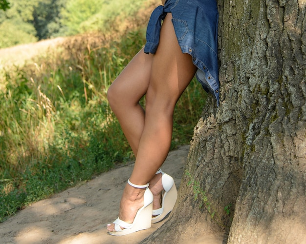 Meisje in korte broek en witte schoenen poseren in de buurt van hout in de natuur