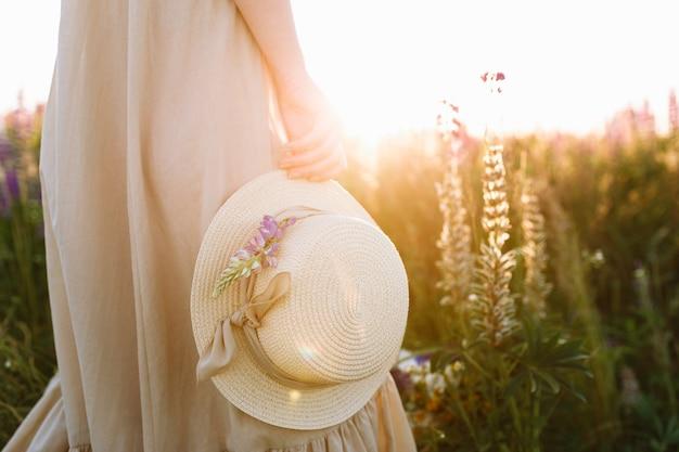 Meisje in lange jurk bedrijf strooien hoed staande in voorjaar bloem veld bij zonsondergang
