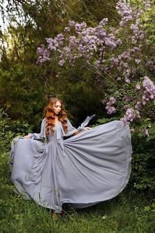 Meisje in lange jurk in de buurt van lila op groene zomer achtergrond