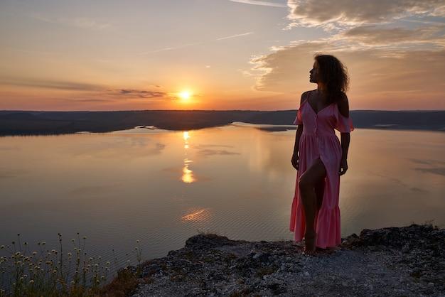 Meisje in lange roze jurk op rots over meer in de avond.