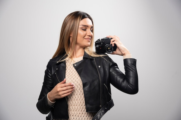 Meisje in leren jas die haar foto's in elegante en positieve posities neemt.