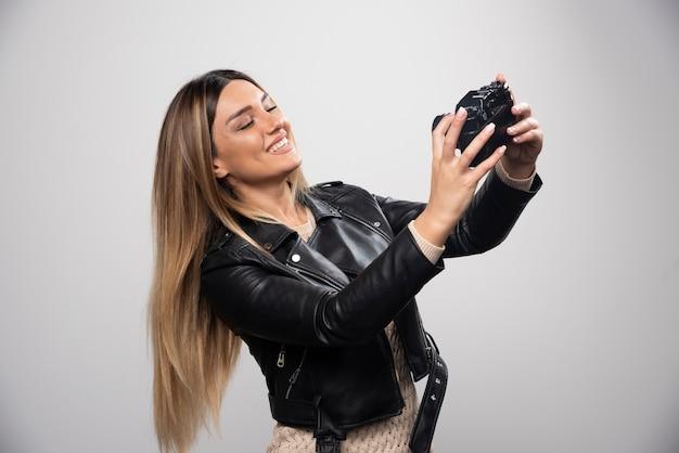 Meisje in leren jas die haar foto's in elegante en positieve posities neemt