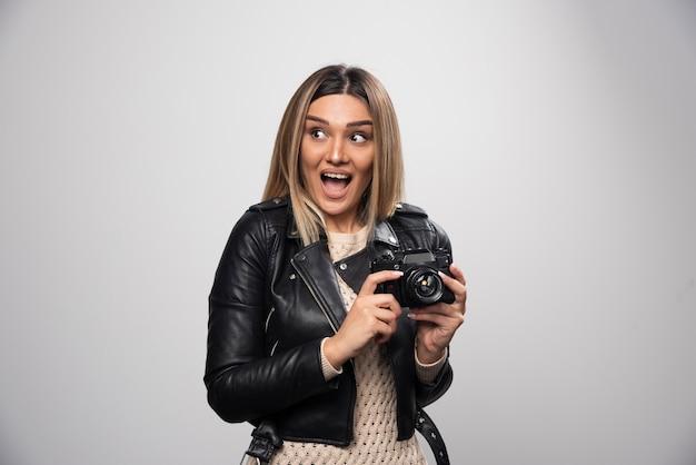 Meisje in leren jas die haar foto's in grappige en vreemde posities neemt