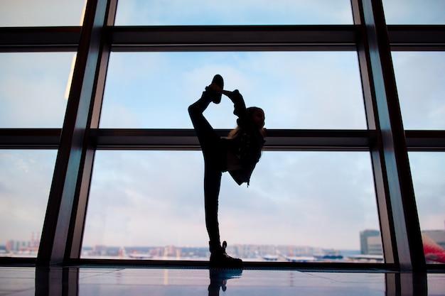 Meisje in luchthaven dichtbij groot venster terwijl wacht op het inschepen
