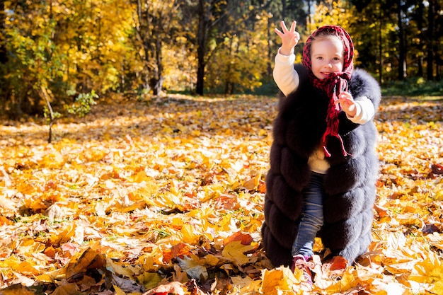Meisje in mama's vest in herfst park