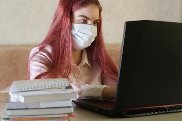 Meisje in medisch masker dat thuis gebruikend laptop bestudeert. thuisschool, online onderwijs, thuisonderwijs, quarantaine van het coronavirus.