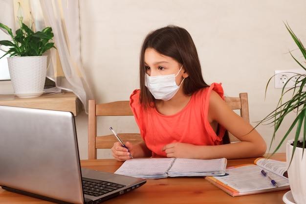 Meisje in medisch masker op haar gezicht dat huiswerk doet en op webinar bij laptop let. onderwijs op afstand, thuisonderwijs, e-learning thuis tijdens quarantaineconcept