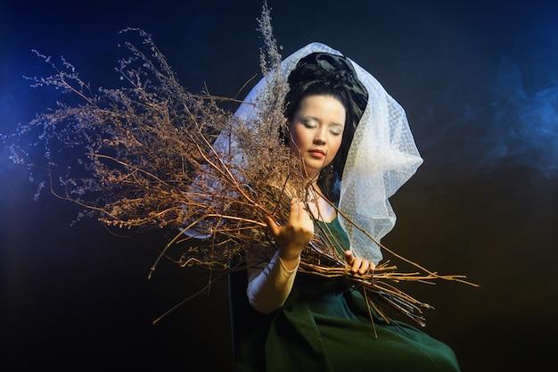 Meisje in middeleeuwse jurk met bos van stokken