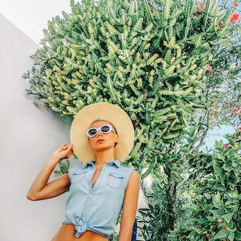 Meisje in mode-zomeraccessoires en jeansoutfit op cactuslocatie reis zomerstemming