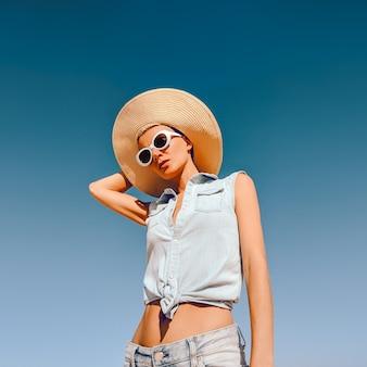 Meisje in modeaccessoires. hoed en zonnebril en jeans outfit. strand zomerstemming
