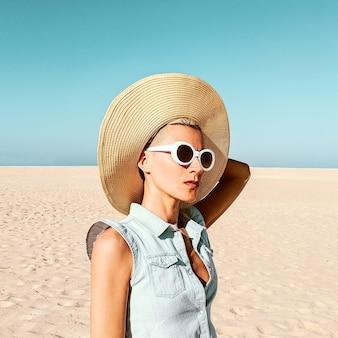 Meisje in modeaccessoires. hoed en zonnebril. strandstemming