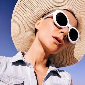Meisje in modeaccessoires. hoed en zonnebril. strandstemmingsvibes