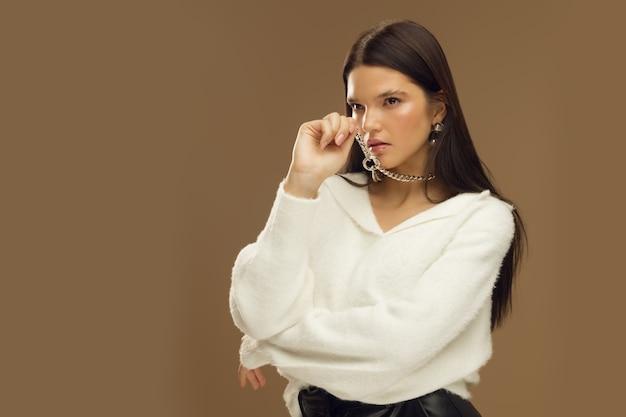 Meisje in modieuze kleding en met een enorme ketting, studiofotografie, mode en stijl, moderne damesmode. hoge kwaliteit foto