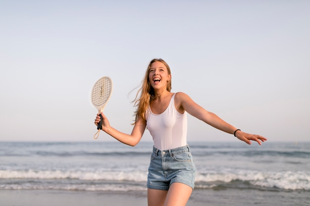 Meisje in mouwloos onderhemd en borrels die tennis spelen bij kust