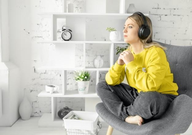 Meisje in oortelefoons in gele blouse zit ontspannen op grijze bank om muziek of online cursussen te luisteren, te dromen of geweldige momenten terug te roepen. witte bakstenen muur achtergrond.