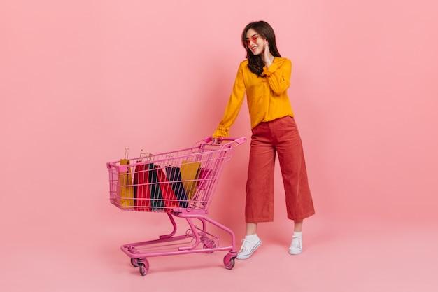 Meisje in oranje blouse en zonnebril met glimlach kijkt naar veel van haar aankopen liggend in roze trolley van supermarkt.