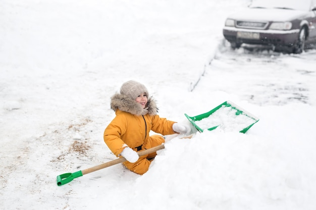 Meisje in oranje jumpsuit maakt sneeuw grote schop schoon