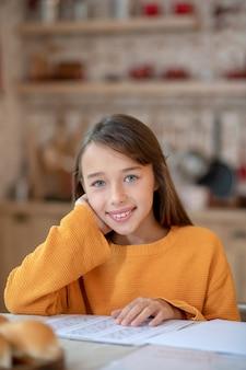 Meisje in oranje overhemd positief gevoel tijdens huiswerk