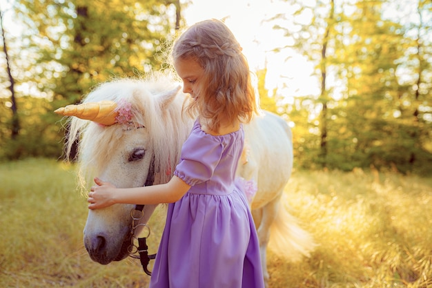 Meisje in paarse jurk knuffelen witte eenhoorn paard. dromen komen uit. sprookje