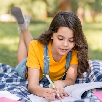 Meisje in park dat thuiswerk doet