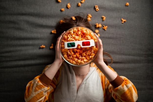Meisje in pyjama eet popcorn, ligt op een grijze achtergrond in 3d-bril en kijkt naar een film