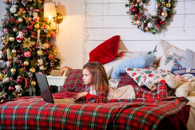 Meisje in pyjama ligt op een bed op een rode plaid van een kerstboom en kijkt naar de monitor van de laptop.