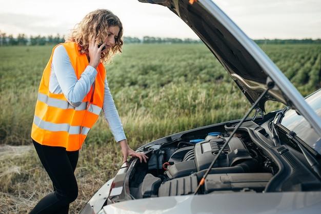 Meisje in reflecterend vest met telefoon, kapotte auto
