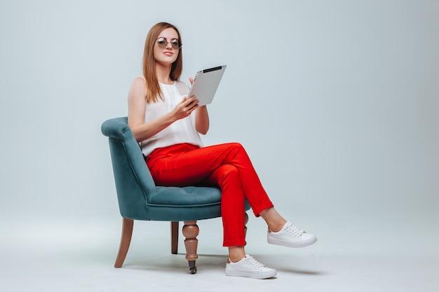 Meisje in rode broek zittend in een stoel en met behulp van haar tablet