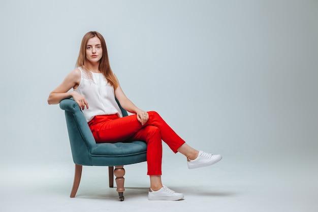 Meisje in rode broek zittend in een stoel op een lichtgrijze achtergrond