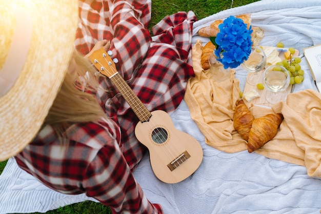 Meisje in rode geruite jurk en hoed zittend op een witte gebreide picknickkleed speelt ukelele en het drinken van wijn
