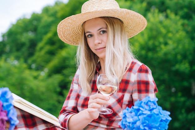 Meisje in rode geruite jurk en hoed zittend op wit gebreide picknickdeken leesboek en het drinken van wijn.